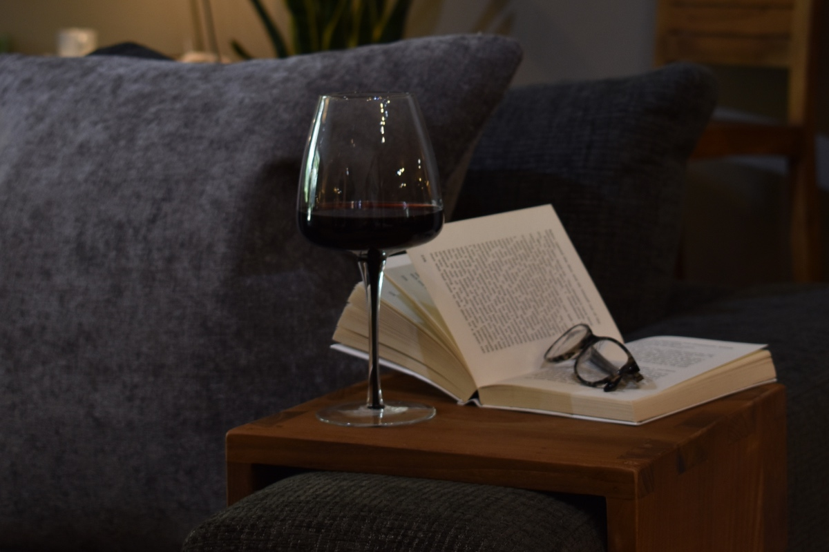 Book on teak armrest with glass of red wine