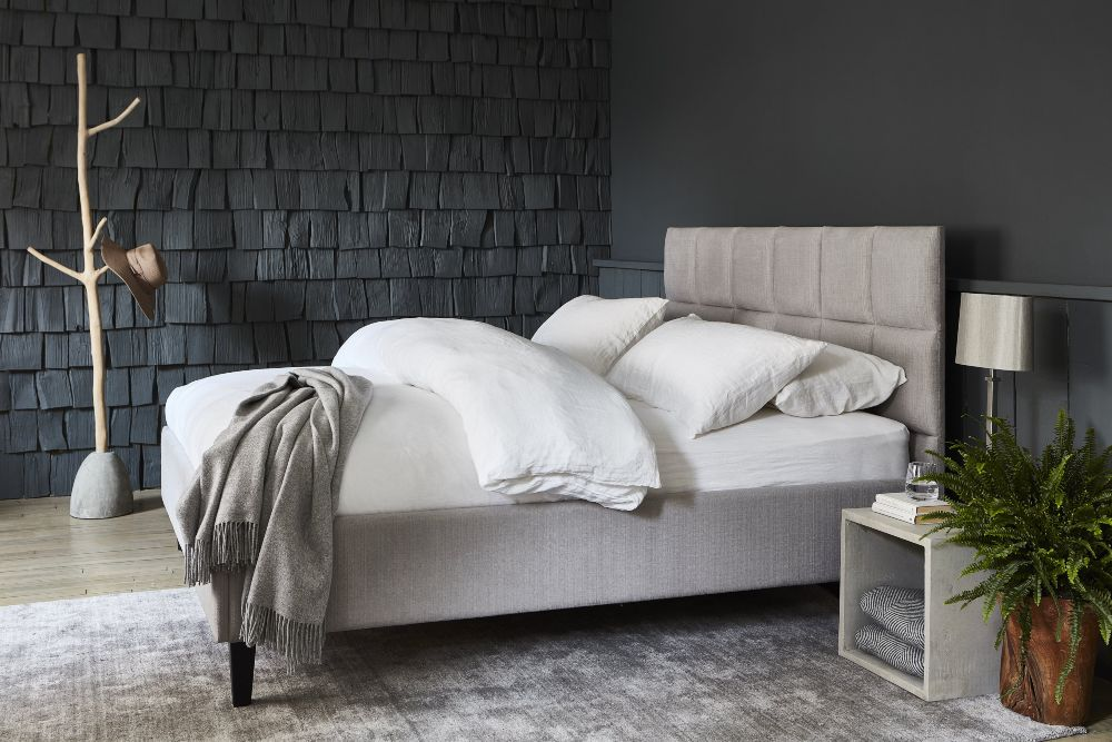 Raft Furniture upholstered bed with feature wall with concrete storage cube and table lamp