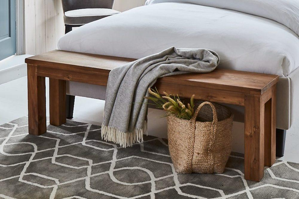 self care soft throw in a wooden bench at the end of the bed