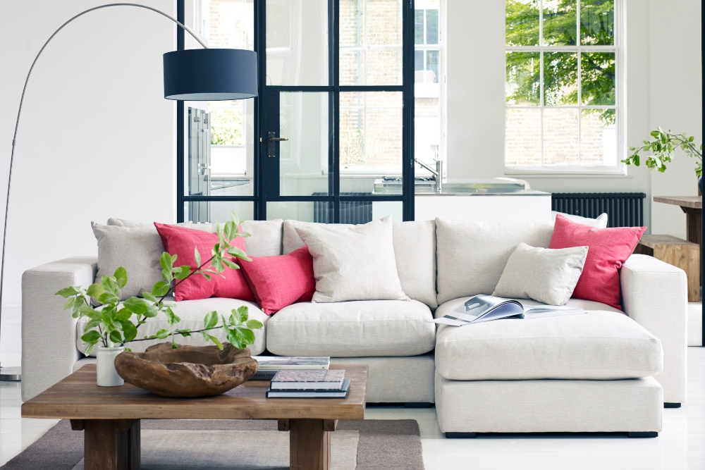 7 best sofas of 2021 Raft Furniture white Loft corner unit and pink scatter cushions and crittall lamp