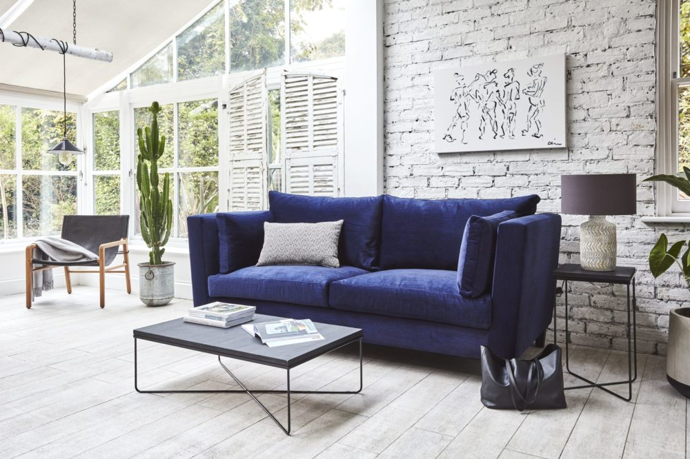 mid-century modern interiors with bright blue high arm sofa and coffee table to show retro style sofa