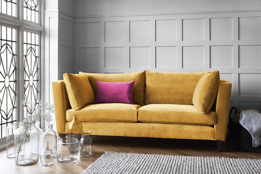 Mustard yellow sofa with high arms to show bright colours trend in 1950s interior design
