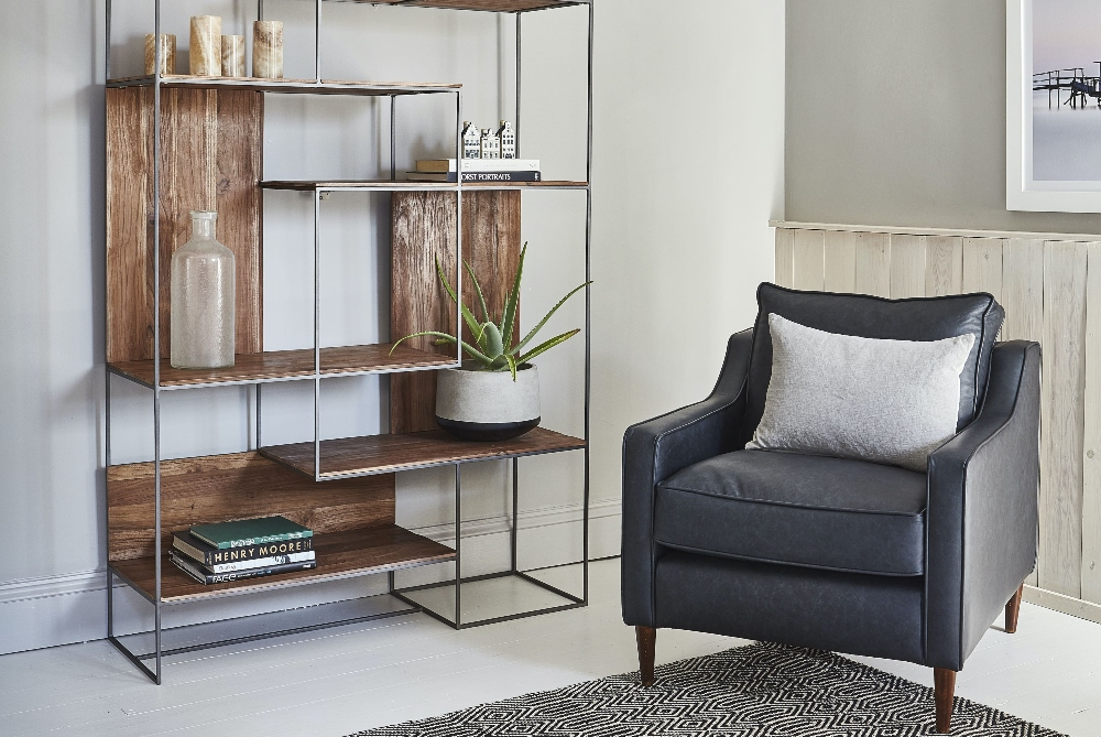 Mid-century modern interiors with small leather armchair and sculptural bookcase for interior design statement