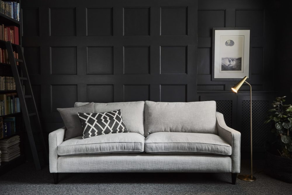 Mid-century modern interiors grey sofa with black feature wall and bookcase to show retro style living room